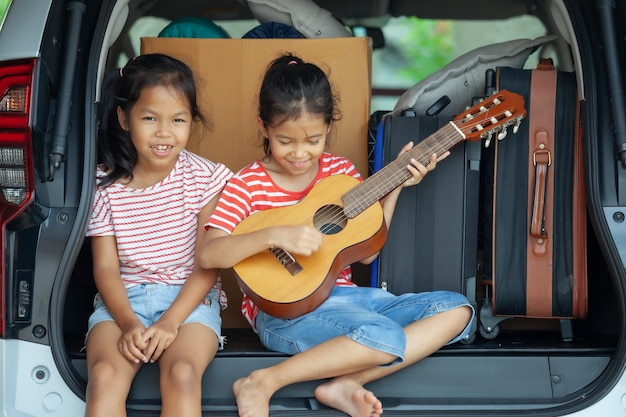 Asian child girl playing guitar and singing a song with her sister in a car trunk