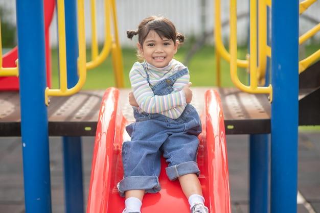 야외 놀이터에서 노는 아시아 어린이 소녀. 아이들은 학교나 유치원 마당에서 놀고 있습니다. 어린이를 위한 건강한 여름 활동.