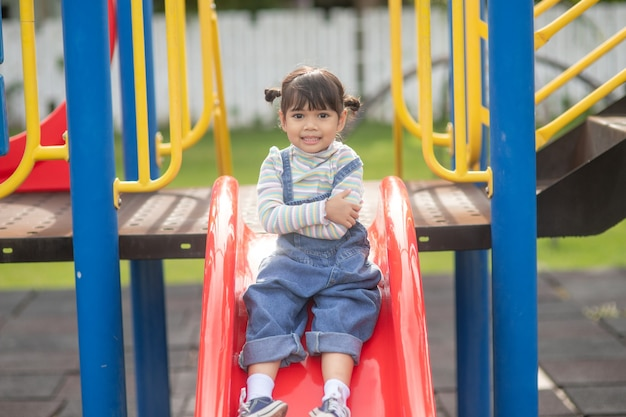 Asian child girl playing on the outdoor playground. kids play in school or kindergarten yard. healthy summer activity for children.
