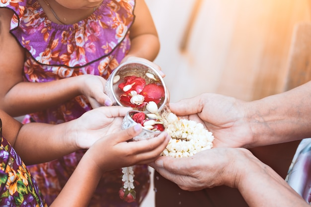 アジアの子供の女の子が高齢の老人や敬虔な祖父母の手に水を注ぐ