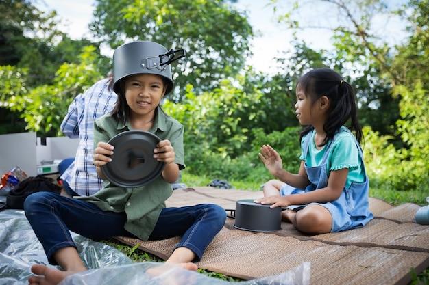아시아 아이 소녀 머리에 냄비 덮개를 씌우고 그녀의 부모 요리를 돕는 재미