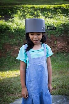 Азиатская девочка-девочка накинула крышку на голову и развлекается, чтобы помочь родителям готовить