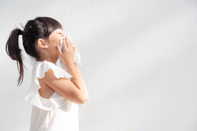 Asian child girl sick with sneezing on the nose and cold cough on tissue paper because weak or virus and bacteria from dust weather
