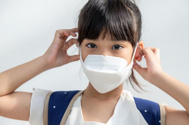弱いので、鼻にくしゃみをし、ティッシュペーパーに風邪をひいて病気のアジアの子供の女の子