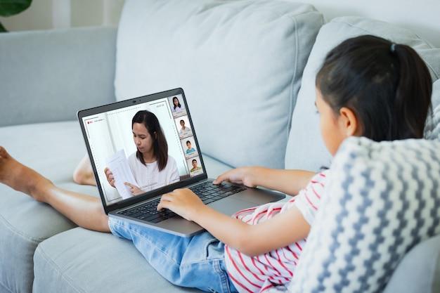 ソファに座って、教師やクラスグループとビデオ会議チャットをしているアジアの子供の女の子。子供は、コロナウイルスcovid-19の発生により、検疫中に自宅からホームスクーリングの研究を行っています。