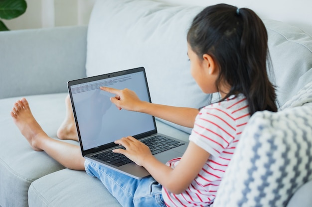 Asian child girl sitting on sofa and doing her homework in computer laptop. child homeschooling study from home during quarantine due to covid-19 outbreak.