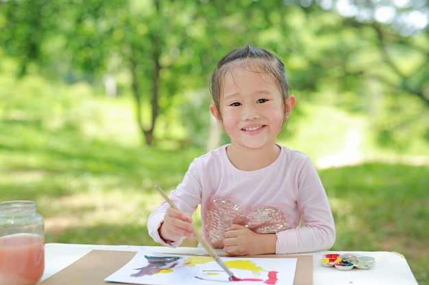 Asian child girl sitting at a table in a summer garden painting with paintbrush