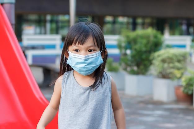 Азиатская девочка улыбается и носит тканевую маску, она играет с игрушкой-ползунком на детской площадке
