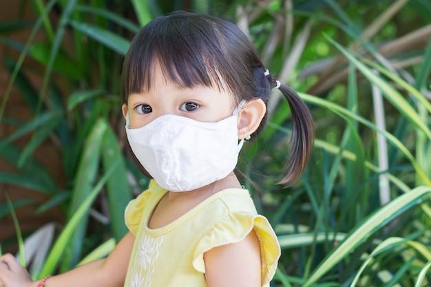 Азиатская девушка ребенка усмехаясь и нося маску ткани,