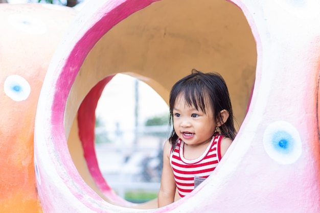 Asian child girl smiling and laughing. she playing with the toy at the park playground.