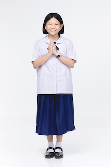 Asian child girl in student's uniform, acting sawaddee mean hello .