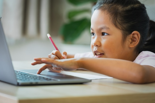 アジアの子供女の子の学生は、ビデオ通話で教師とオンラインで勉強します。子供は、covid 19のパンデミックのため、検疫中にコンピューターのラップトップを使ってホームスクーリングをしています。