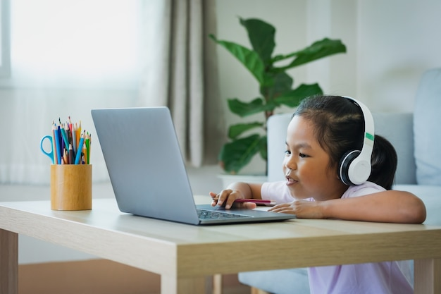 Asian child girl student wear headphone study online with teacher by video call. child is homeschooling with computer laptop during quarantine due to covid 19 pandemic.