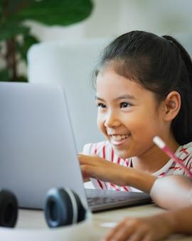 アジアの子供女の子の学生は、ビデオ通話で教師とオンラインでヘッドフォンの勉強をします。子供は、covid 19のパンデミックのため、検疫中にコンピューターのラップトップを使ってホームスクーリングをしています。