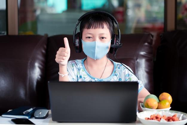 2019-ncov 또는 covid 19 바이러스, 온라인 교육 개념을 보호하기 위해 집에서 온라인 수업 중에 숙제를 하고 얼굴 마스크를 쓴 아시아 소녀