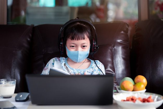 Asian child girl studying homework and wearing face mask during her online lesson at home for protect 2019-ncov or covid 19 virus , online education concept.