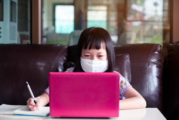 Asian child girl studying homework and wearing face mask during her online lesson at home for protect 2019-ncov or covid 19 virus