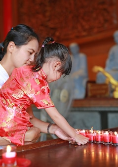 Asian child girl in traditional dress light the worship candles at chinese temple
