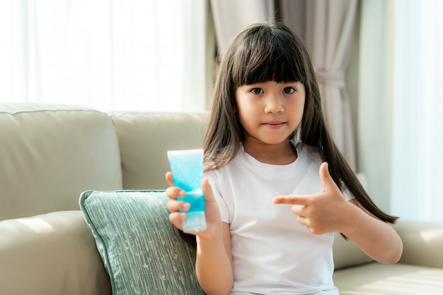 Asian child girl using alcohol antiseptic gel, prevention, cleaning hands frequently, prevent infection, outbreak of covid-19