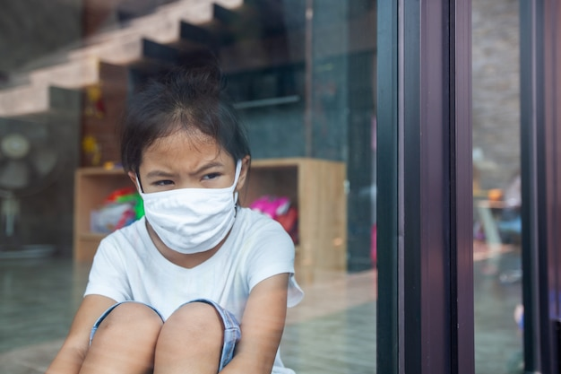 Asian child girl wearing protection mask looking outside through the window and stay at home quarantine from the coronavirus covid-19 and air pollution pm2.5.