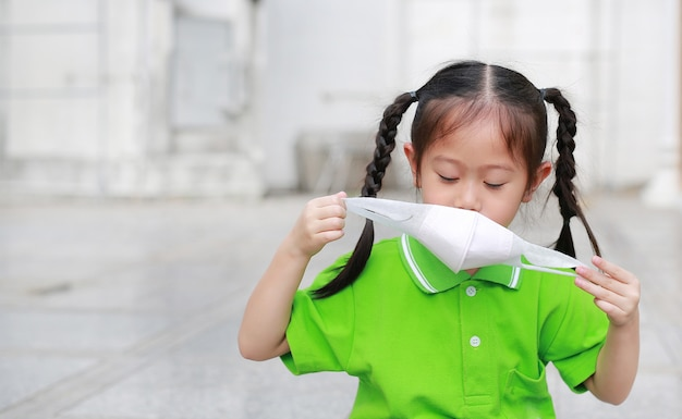 Asian child girl wearing a protection mask while outside to against air pollution.