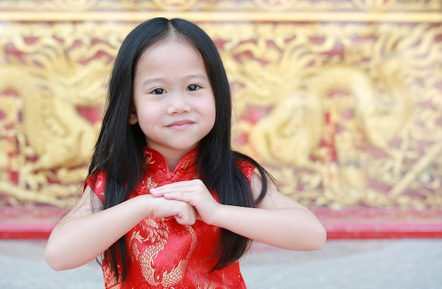 Asian child girl wearing red cheongsam with greeting gesture celebration