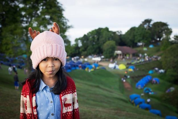Азиатская детская девочка в теплой шляпе, стоящая на холме с зеленой травой