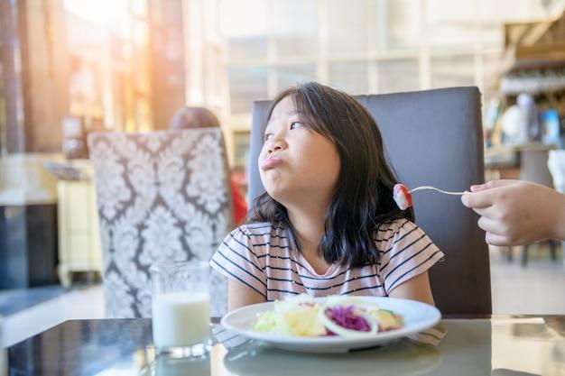Азиатская детская девочка с выражением отвращения к помидору в салате, отказ от еды