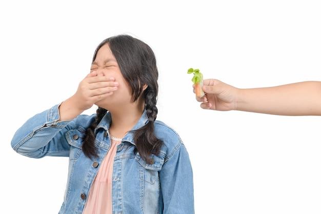 Азиатская детская девочка с выражением отвращения к овощам в салате, отказ от еды