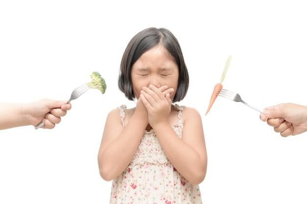 흰색 배경에 고립 된 야채에 대한 혐오의 표정으로 아시아 아이 소녀, Refusin 프리미엄 사진