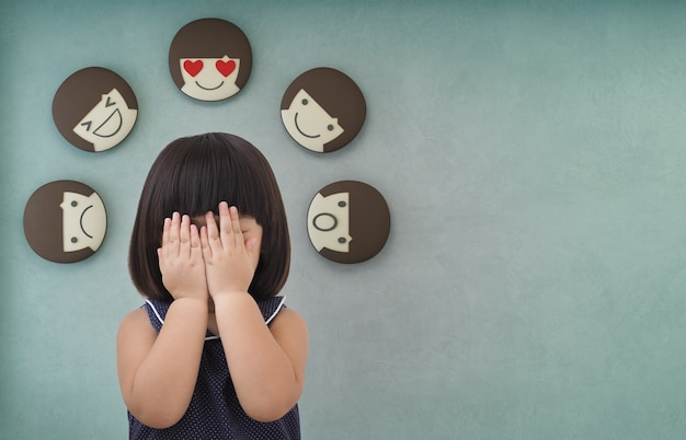 Asian child girl with green concrete wall background, feelings and emotions of kid.