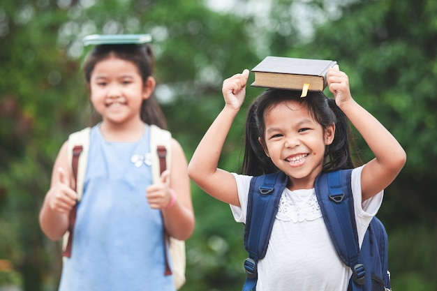 Asian child girl with school bag and her sister put a book on head together