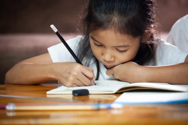Азиатский ребенок девочка писать и делать домашнее задание дома. образование из дома концепции.