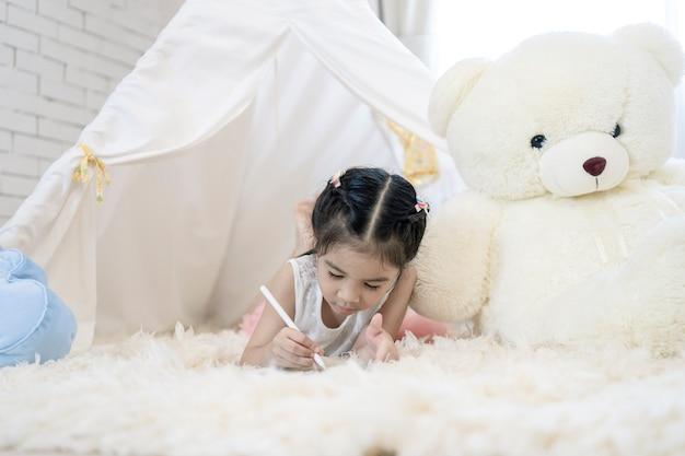 Азиатское сочинительство девушки ребенка на умной таблетке. инновационные цифровые технологии для обучения современному стилю жизни.