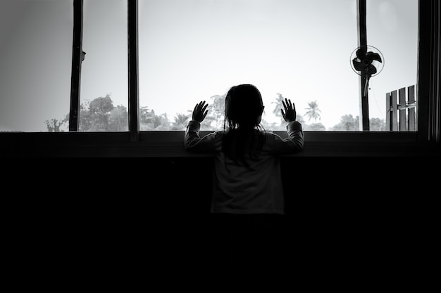 Asian child girls are standing in the dark, looking out the window, sad mood