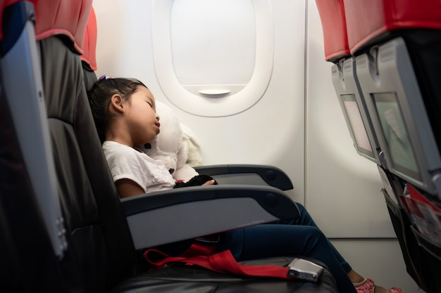 Asian child girls traveling by an airplane. she hugging her doll and sleeping