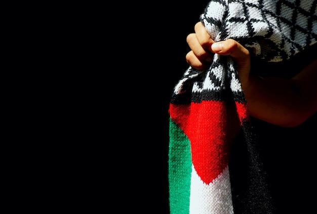 Азиатская детская рука с шарфом флаг палестины, на темном фоне.