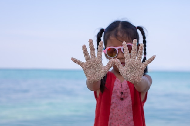 Asian child hands with sand having fun on the beach