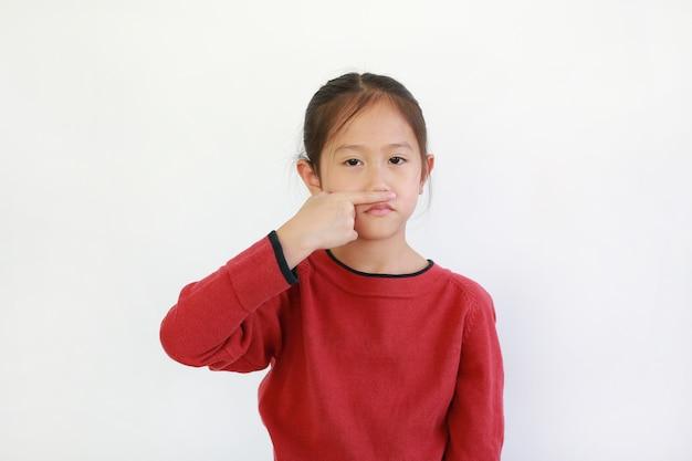 집게 손가락을 들고 아시아 아이 냄새를 맡는 동안 그의 코를 닫습니다