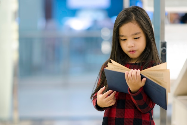Asian child holding open textbook in book store