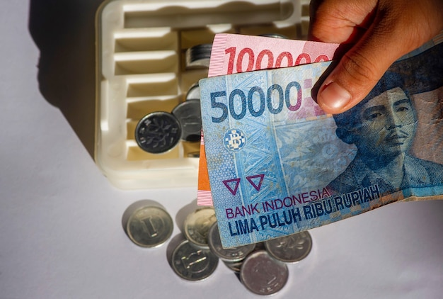 An asian child holds indonesian money, with the coin box background, in shallow focus. saving and giving concept.