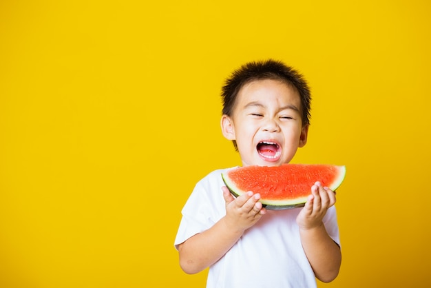Asian child little boy laugh smile holds cut watermelon fresh for eating