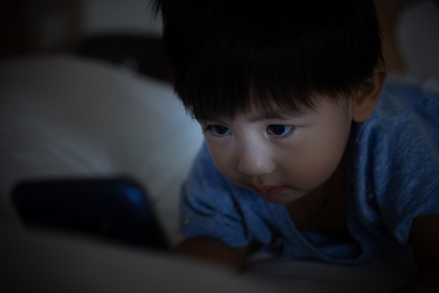 Asian child lying on bed and playing on mobile phone