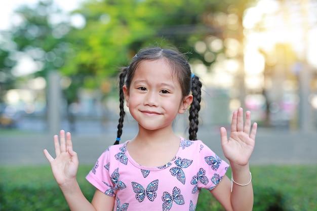 아시아 어린이 또는 아이 소녀 미소와 야외 정원에서 그녀의 손을 보여줍니다.