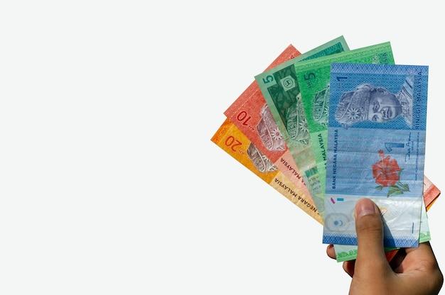 Рука азиатского ребенка, держащая деньги малайзии, изолированные на белом фоне