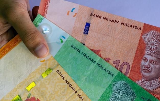 Рука азиатского ребенка, держащая деньги ринггит малайзии, в мелком фокусе.