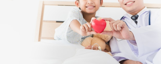 Asian child's hand and male doctor hold red heart lying on bed in the hospital.