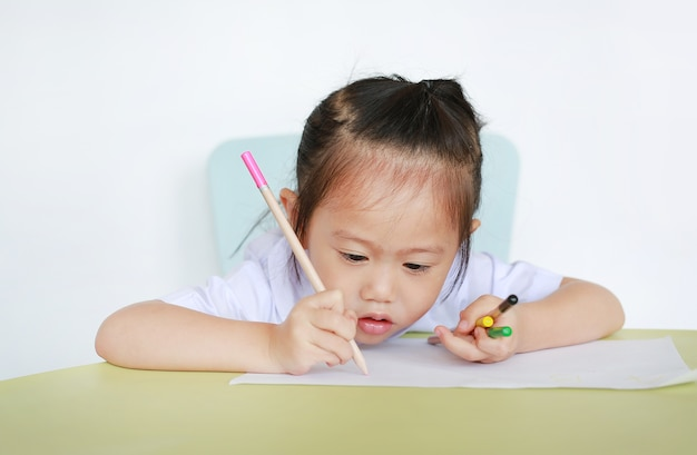 Asian child in school uniform with pencil writing on table isolated on white background.