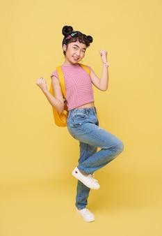 아시아 어린이 학생 제스처는 노란색 배경에 고립 된 행복 한 축하. 승자 개념입니다.