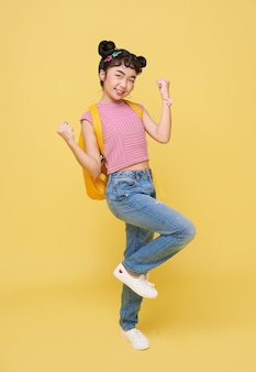 Asian child student gesture happy celebrating isolated on yellow background. winner concept.